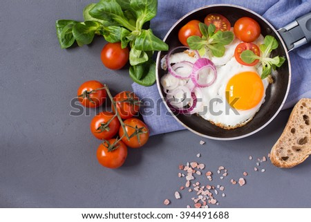 Fried eggs with tomatoes, herbs, onion, bread. Top view with copy space - stock photo
