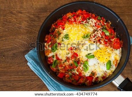 fried eggs with vegetables and cheese in a frying pan on wooden table - stock photo