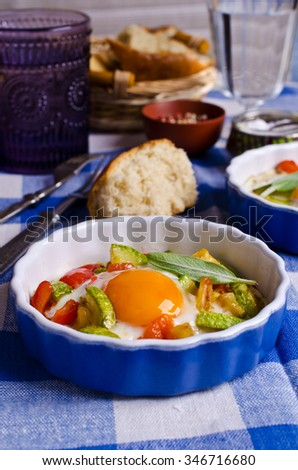 Fried eggs with vegetables in a batch container. Selective focus.