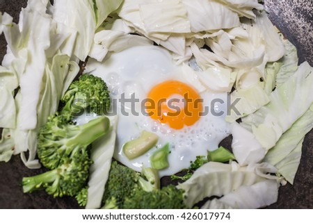 Fried eggs with vegetables on a frying pan  - stock photo