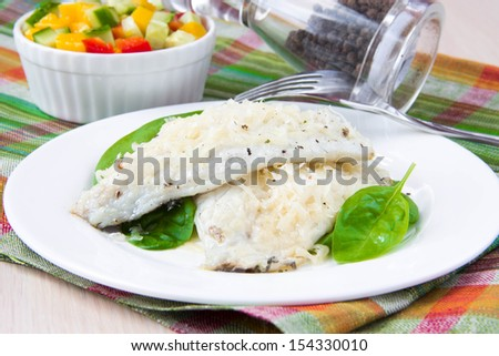 Fried filet of white fish Dorado on bed of fresh spinach and salsa with mango, cucumber and red pepper - stock photo