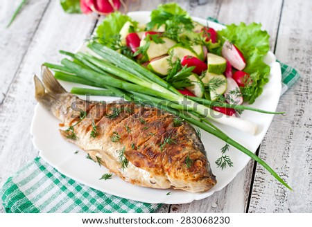 Fried fish carp and fresh vegetable salad - stock photo