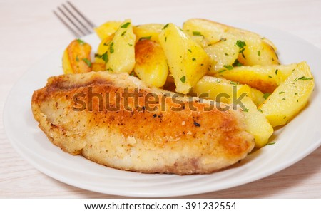 Fried fish fillet and potatoes in a plate