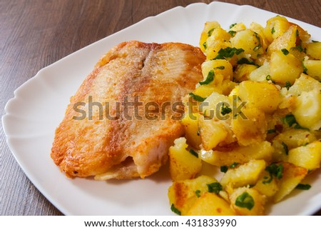 Fried fish fillet and potatoes in a plate on wooden table