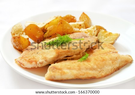 Fried fish fillet with baked potatoes on white plate - stock photo