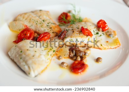 Fried fish fillet with capers and tomatoes in plate - stock photo