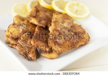 fried fish fillet with lemon on a white plate