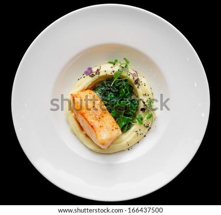 Fried fish fillet with potato mash isolated on black background - stock photo