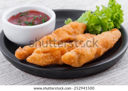 Fried fish fingers with sauce - stock photo