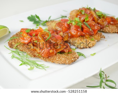 fried fish herring with tomato sauce on a plate