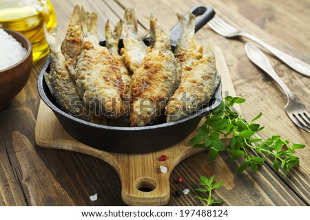 Fried fish in a frying pan on the table  - stock photo
