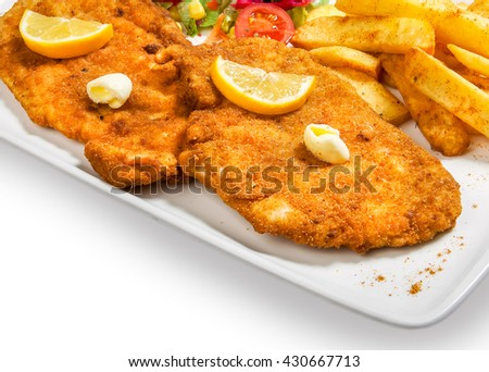 fried fish in breadcrumbs with potatoes fries and vegetables in a plate on white background