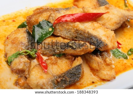 Fried fish in spicy curry sauce on white dish