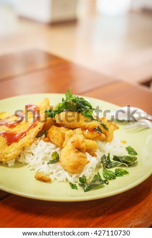 fried fish , Kaffir lime fried and rice in a restaurant, Thai Foods. A diet consisting of various herbs . Rich and varied