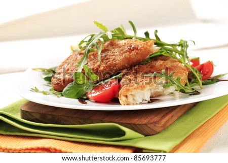 Fried fish on a bed of fresh salad - stock photo