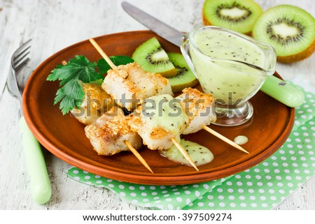 Fried fish on bamboo skewers with kiwi sauce selective focus - stock photo