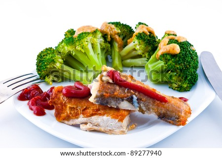 Fried fish poured ketchup, not near a plate with a grainy mustard broccoli