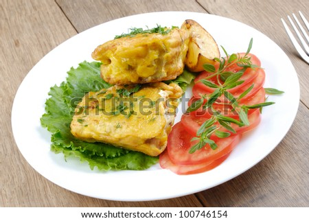 Fried fish served with tomatoes closeup