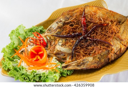 Fried fish topped with chili, vegetable dish.