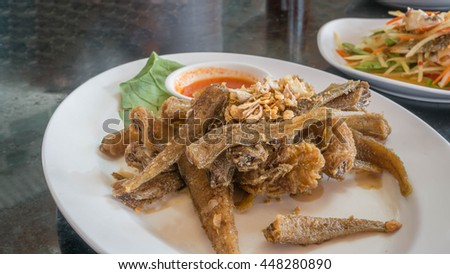 Fried fish topped with garlic served on dish with chili sauce - stock photo