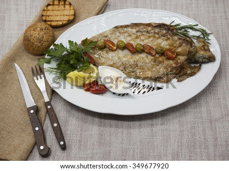Fried fish whitefish on plate with vegetables and bread with a fork and knife - stock photo