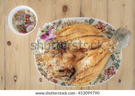 Fried fish with fish sauce on the table - stock photo