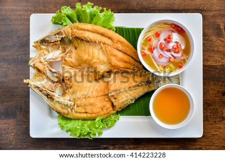 Fried fish with fresh herbs and sweet spicy sauce - stock photo