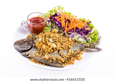 Fried fish with garlic tasty seafood on white plate