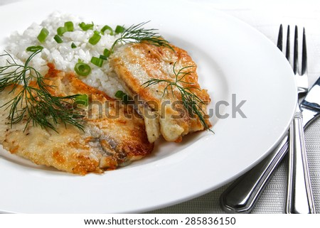 Fried fish with rice on the white plate, shallow focus - stock photo