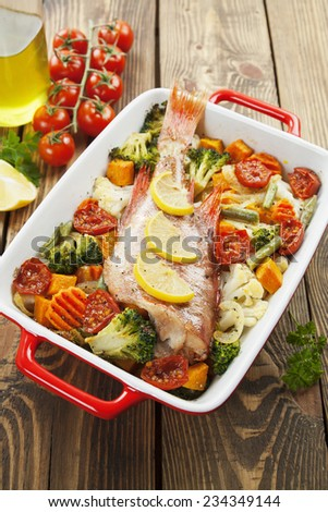 Fried fish with vegetables in the  pot - stock photo