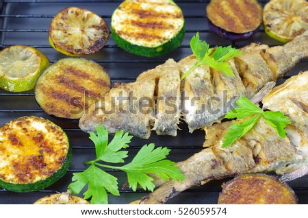 fried fish with vegetables on  grill