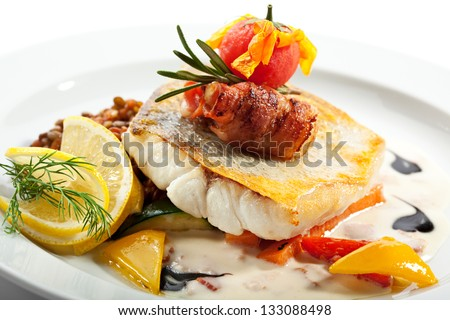Fried Fish (Zander) with Bacon. Garnished with Lemon,  Lentil and Vegetables - stock photo