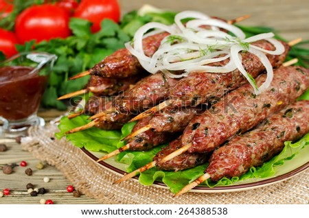 Fried food on wooden skewers and fresh vegetables on wooden table - stock photo