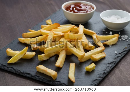 fried French fries, tomato sauce and salt on a blackboard, close-up - stock photo