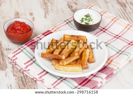 fried french fries with tomato sauce and herbs, close-up, horizontal - stock photo