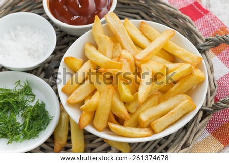 fried french fries with tomato sauce and herbs, top view, close-up - stock photo
