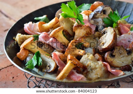 Fried fresh mushrooms, bacon and bread dumplings in a serving pan - stock photo