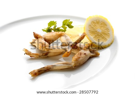 Fried frog legs on white plate - stock photo