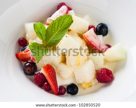 fried fruit salad with mint leaf in white dish