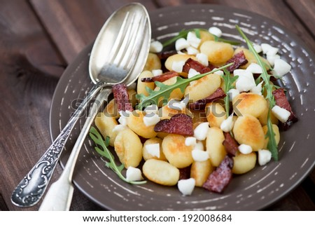 Fried gnocchi with meat, cheese and arugula, horizontal shot