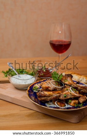Fried grilled meat served with bread, sauces and wine