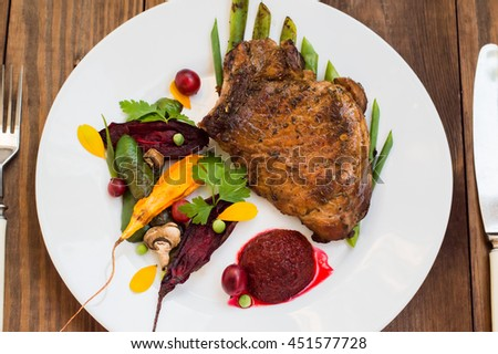 Fried Grilled pork steak on the bone with vegetables, mashed beetroot and berry sauce. Wooden background. Top view. Close-up