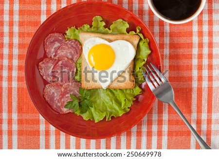 Fried heart shaped egg on toast with salad and coffee for Valentines Day or Easter on table - stock photo