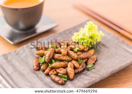 Fried insects - Wood worm insect crispy with pandan after fried and add a light coating of sauce and garnish Thai pepper powder with chopsticks, tea, on wooden background, Select focus