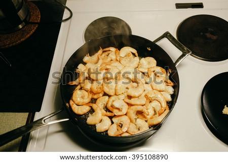 fried king prawns in iron pan - stock photo