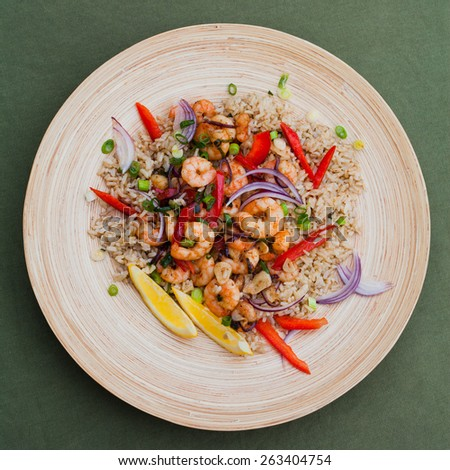 Fried king prawns with brown rice and vegetables: red pepper and onions. Served on a wooden plated with cut chives, spring onions and two pieces of lemon.Macro perspective, nobody, restaurant, menu.  - stock photo