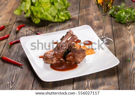 Fried lamb ribs on white plate on wooden background with lettuce.