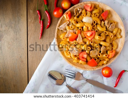 Fried macaroni with pork and vegetable in tomato sauce in plate placed on a wooden table - stock photo