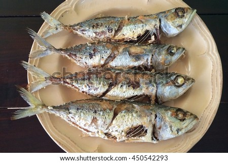 Fried mackerel in plate on a wooden table.