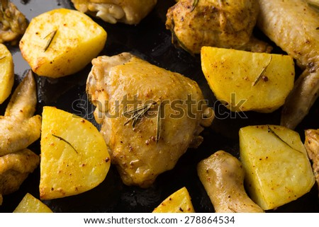 Fried meat and potatoes with spices on the pan - stock photo